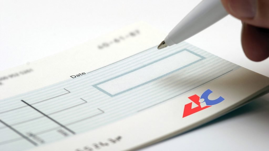 blank cheque being signed with AiC logo
